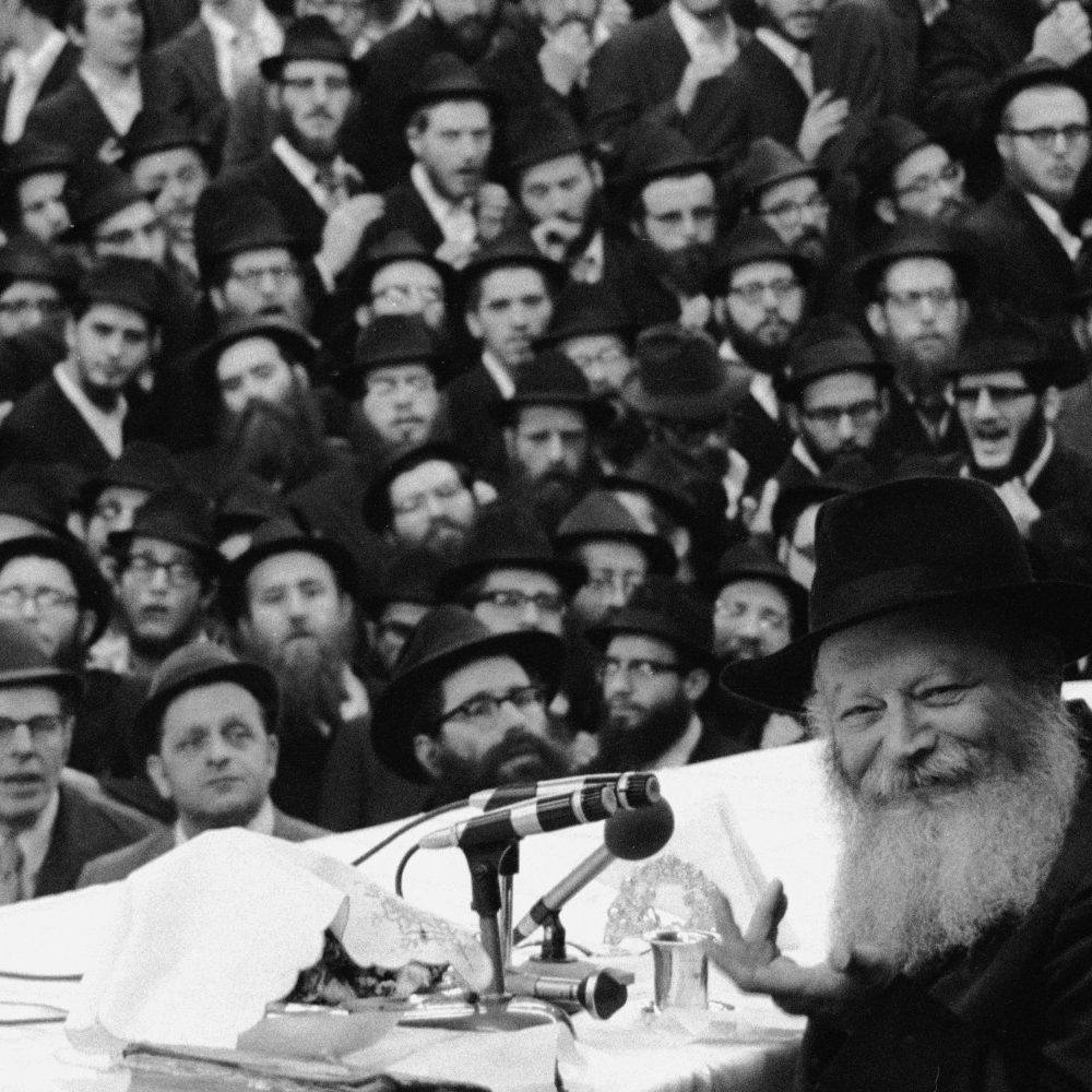 Russian-born Orthodox Jewish Rabbi Menachem Mendel Schneerson (1902 - 1994) smiles and gestures at the camera from behind several microphones on a table while his audience watches, New York, 1970s. (Photo by Tim Boxer/Getty Images)